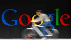 File photo of an employee riding her bike past a logo next to the main entrance of the Google building in Zurich