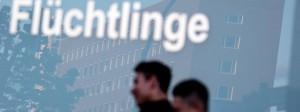 """Zwei Männer gehen vor dem Bundesamt für Migration und Flüchtlinge in der Berliner Bundesallee am Schriftzug """"Migration, Flüchtlinge"""" vorbei."""