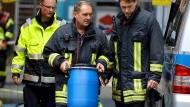 Ein Feuerwehrmann in Köln trägt eine Tonne aus einem Wohnkomplex.