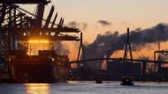 Kurz vor Sonnenaufgang im Hafen in Hamburg: Ein Containerschiff liegt am Terminal Burchardkai, dahinter ist die Köhlbrandbrücke zu sehen.