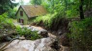 5.Juli, Hessen, Aumenau: Geröll und Wasser haben einen Hang auf ein Wohnhaus rutschen lassen. Heftige Gewitter haben in mehreren Orten im Kreis Limburg-Weilburg für überflutete Straßen und vollgelaufene Keller gesorgt.