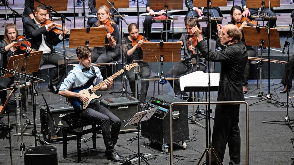 Konzentriert: Yaron Deutsch mit E-Gitarre und  Dirigent Titus Engel  beim Auftaktkonzert.