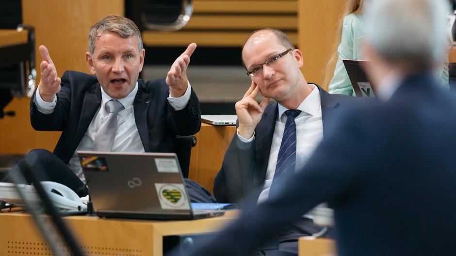 Björn Höcke (links) und Stefan Möller (beide AfD) reagieren bei einer Sondersitzung des Thüringer Landtags zum Verfassungsschutz auf die Rede des Innenministers Georg Maier (SPD).