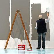 Ein älterer Mann streicht eine Wand.