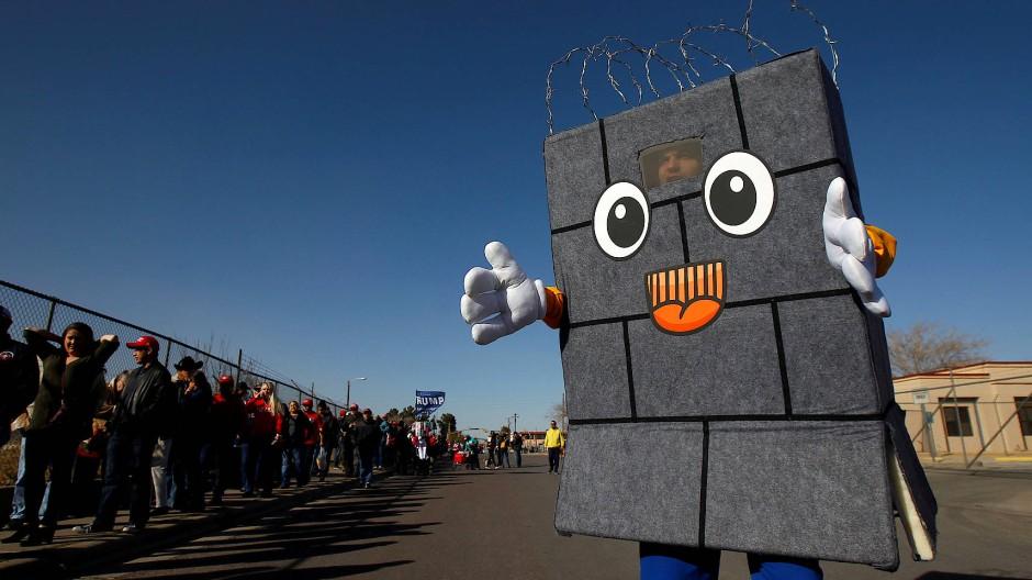 """""""Bricky"""", die leibhaftig gewordene Grenzmauer, ist eine Comicfigur aus der Trevor Noah Show. Hier trifft sie auf Trump-Unterstützer an der Grenze zu Mexiko bei El Paso."""