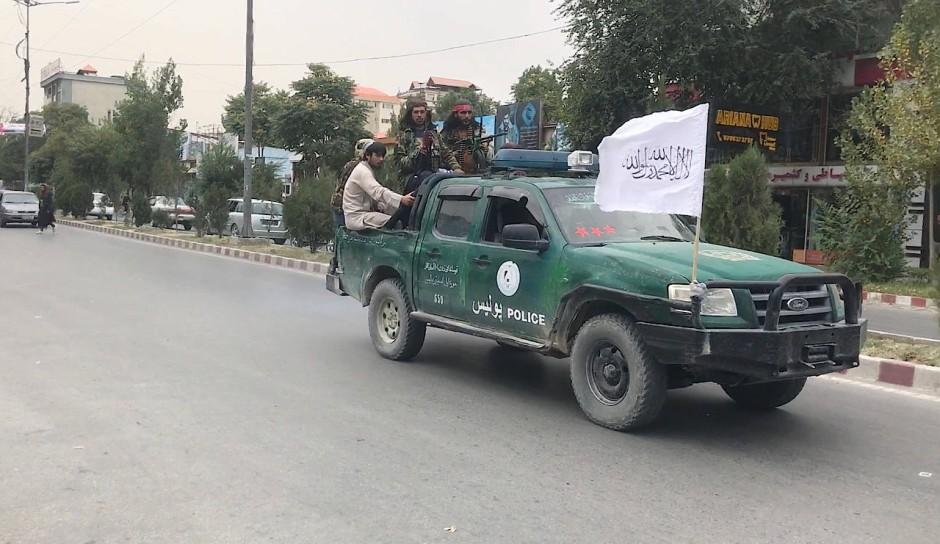 """Taliban fahren auf einem früheren afghanischen Polizeifahrzeug durch ein beliebtes Viertel von Kabul. Wegen der vielen Restaurants und Cafés, der modischen Mädchen und Jungen nannten die Menschen die Gegend Pul-e Surkh """"Klein-Paris""""."""
