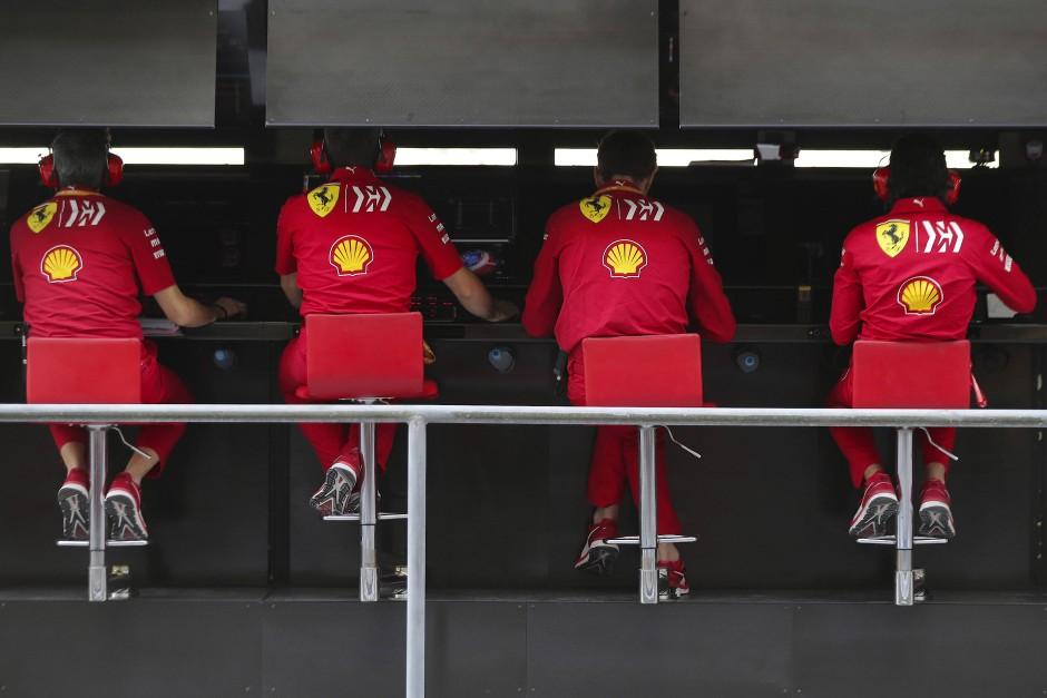 Vier Herren von Ferrari schauen auf ihre Bildschirme.