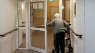 Im hohen Alter werden auch alltägliche Dinge schwierig: Ein Pflegeheim-Bewohner hält sich an seinem Rollator fest, während er die Tür aufmacht.