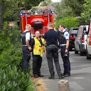 Einsatzkräfte stehen auf einer Straße in Greven, wo zwei Geschwister in einem Gartenteich ertrunken sind.