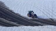 Ein Landwirt bringt Gülle auf einem verschneiten Feld bei Seiffen im Erzgebirge aus.