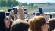 Immer auf Empfang, immer auf Sendung: Smartphone-Nutzer beim Musikfestival Lollapalooza in Berlin
