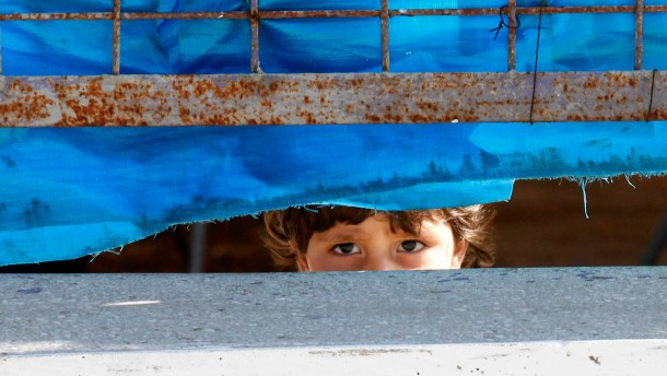 A Syrian refugee girl looks out from behind the fence at Yayladagi refugee camp in Hatay province near the Turkish-Syrian border