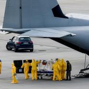 Medizinische Helfer bringen einen Corona-Patienten aus Italien am Dresdner Flughafen von Bord eines Bundeswehrflugzeugs.