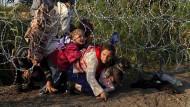 August 2015 steht der Grenzzaun zur ungarischen Grenze nahe Roszke in Serbien. Diese syrischen Flüchtlinge lassen sich davon nicht aufhalten