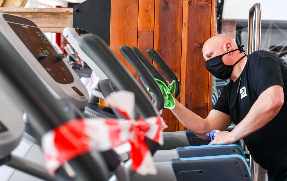 Alles wird desinfiziert: Ein Mitarbeiter in einem Berliner Fitnessstudio