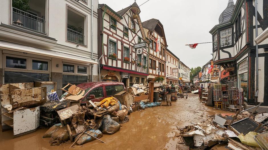 Bad-Neuenahr-Ahrweiler: Anwohner und Ladeninhaber versuchen, ihre Häuser vom Schlamm zu befreien und unbrauchbares Mobiliar nach draußen zu bringen.