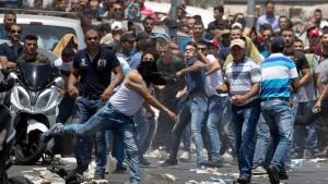 Palästinensische Demonstranten werfen nach den Freitagsgebeten in der Altstadt Jerusalems Steine in Richtung der israelischen Sicherheitskräfte.