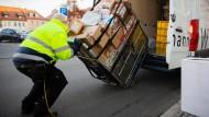Ganz schön viele Pakete: Mitarbeiter eines Paketdienstes schiebt im südbrandenburgischen Kreis Oberspreewald-Lausitz einen Paketwagen in einen Transporter.