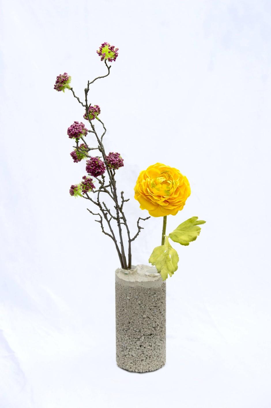 Die Blumenvase in Industriegrau hat ihre Form durch eine leere Chipsdose bekommen.