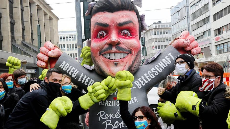 Mitarbeiterinnen von Galeria Kaufhof schlagen am Tag der Schließung ihrer Filiale in Düsseldorf auf eine Pappfigur von Firmeneigner Rene Benko ein.