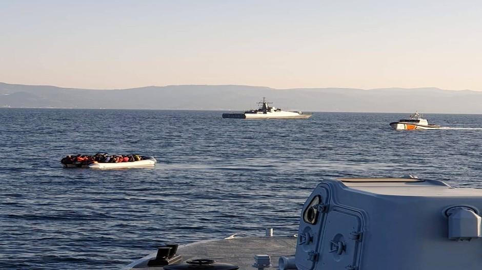 Das Foto der griechischen Küstenwache zeigt ein Migrantenboot mit türkischen Schiffen im Hintergrund am Freitag im Gewässer vor Lesbos.