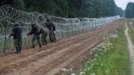 Polnische Soldaten errichten einen Zaun an der Grenze zu Belarus.