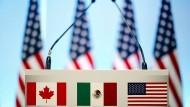 Die Flaggen von Kanada, Mexiko und den Vereinigten Staaten auf einem Rednerpult.