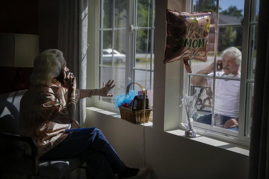 Auf der ganzen Welt erschwerte das Coronavirus 2020 Besuche. In Smyrna, Vereinigte Staaten, winken sich eine Mutter und ihr Sohn durch die Scheibe zu und telefonieren dabei.