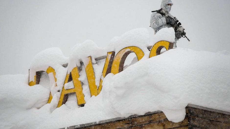 Sicherheitsaufgebot für das Treffen der Elite in den Schweizer Bergen. Ein bewaffneter Wachmann im Schnee-Camouflage-Outfit (Archivbild)