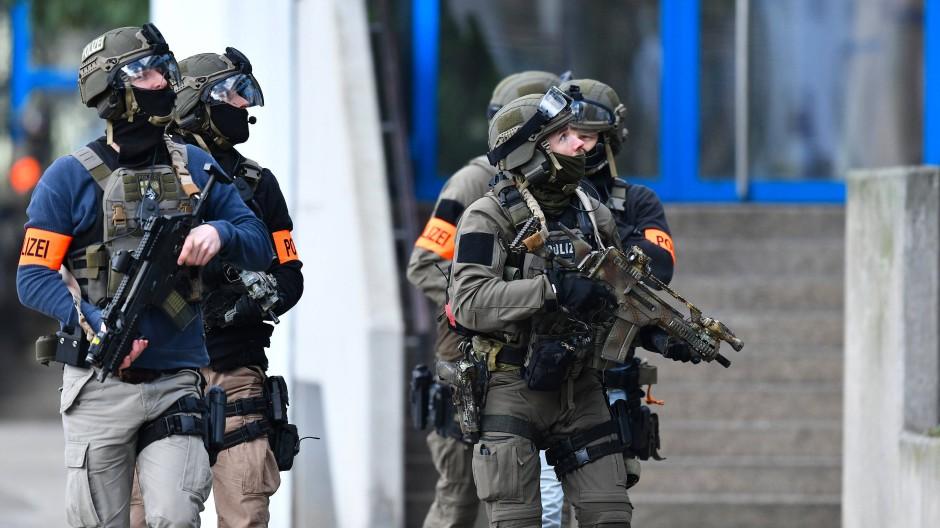 Schwer bewaffnete Beamte eines Spezialeinsatzkommandos gehen in die Karolina-Burger-Realschule.