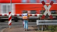 Ein Grundschulkind wartet an einem Bahnübergang auf das Vorbeifahren eines Regionalzuges.