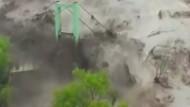Reißende Fluten zerstören Straßen und Häuser
