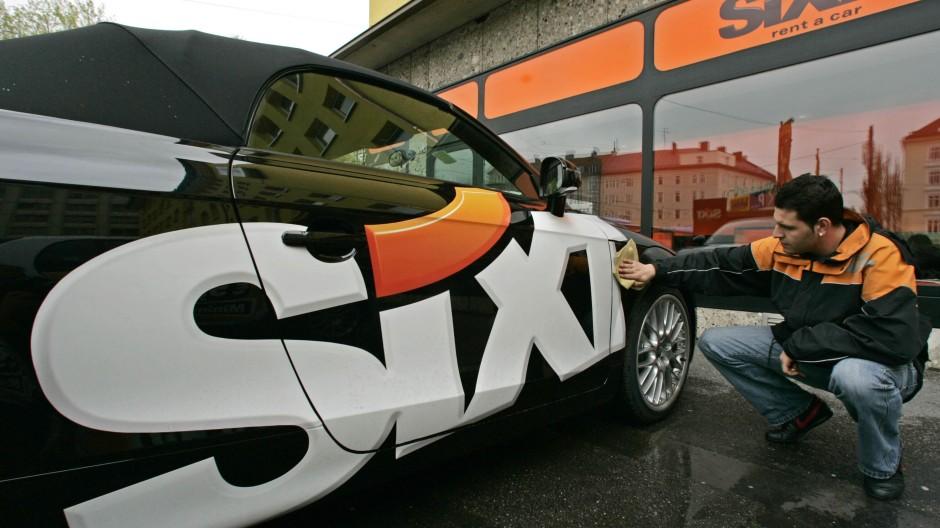 Ein Mitarbeiter des Autovermieters Sixt poliert in einer Filiale des Unternehmens in München das Firmenlogo an einem Mietwagen.