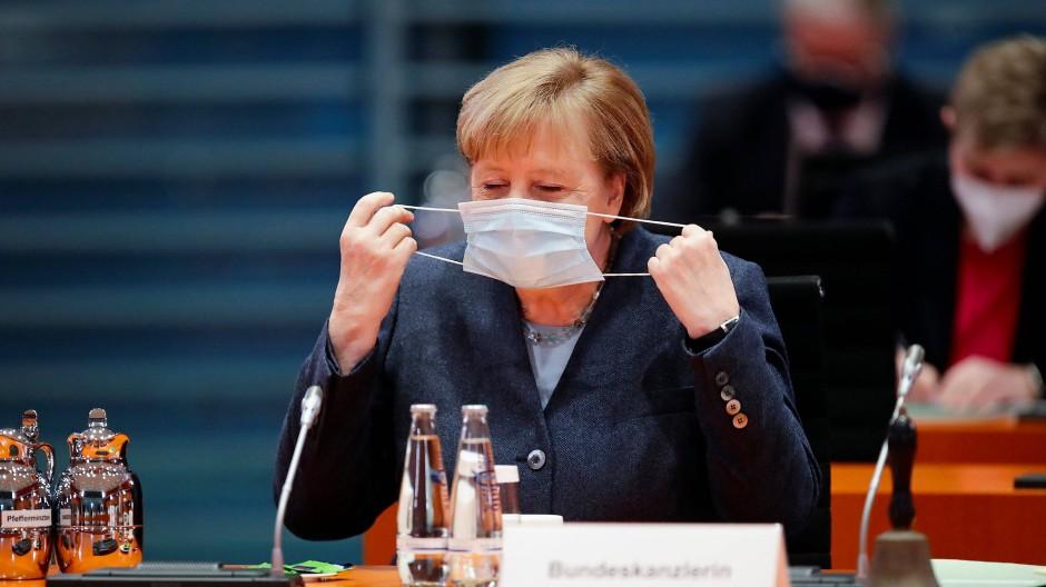 Bundeskanzlerin Angela Merkel nimmt zu Beginn einer Kabinettssitzung ihre Mund-Nasenbedeckung ab.