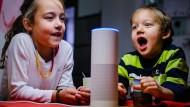 Zwei Kinder sitzen am heimischen Wohnzimmertisch vor dem Sprachassistenten Alexa von Amazon.