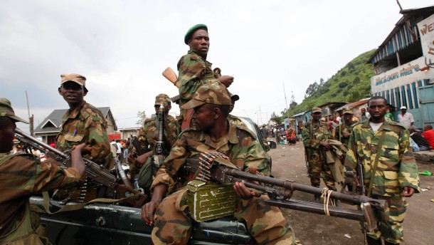 Congolese Revolution Army rebels sit in a truck as they patrol a street in Sake