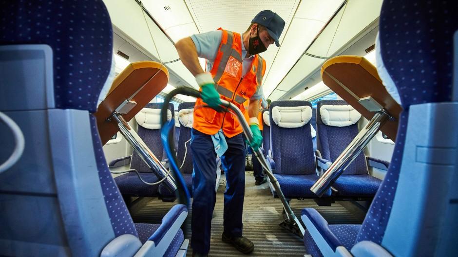 Ein Mitarbeiter des DB-Fernverkehrswerk Dortmund saugt mit einem Staubsauger den Fußboden in einem Zugabteil eines ICE-Zuges.