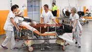 In einem Krankenhaus in Marseille schieben Pflegekräfte eine Patientin in einem Krankenhausbett