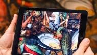 """Auf dem Tablet werden in Brüssels Museen der Schönen Künste Details von Bruegels """"Sturz der Engel"""" sichtbar."""