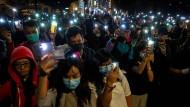 Bei einer Demonstration für die Besetzer der Polytechnischen Universität am Dienstag halten die Menschen ihre Smartphones in die Höhe.