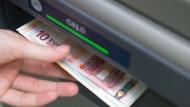 Eine Hand greift nach Geldscheinen, die aus einem Geldautomaten ausgeworfen wurden.