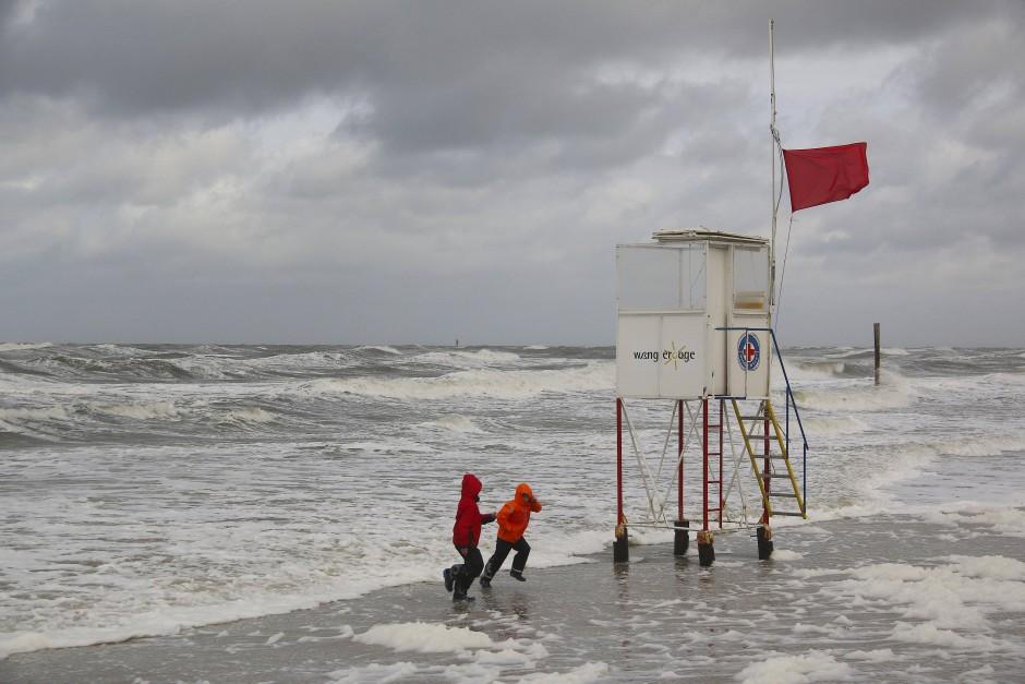 Kinder laufen am Strand von Wangerooge in Niedersachsen bei stürmischen Wind vor den Wellen davon.