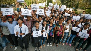 Demonstrators hold placards during a protest in Ahmedabad