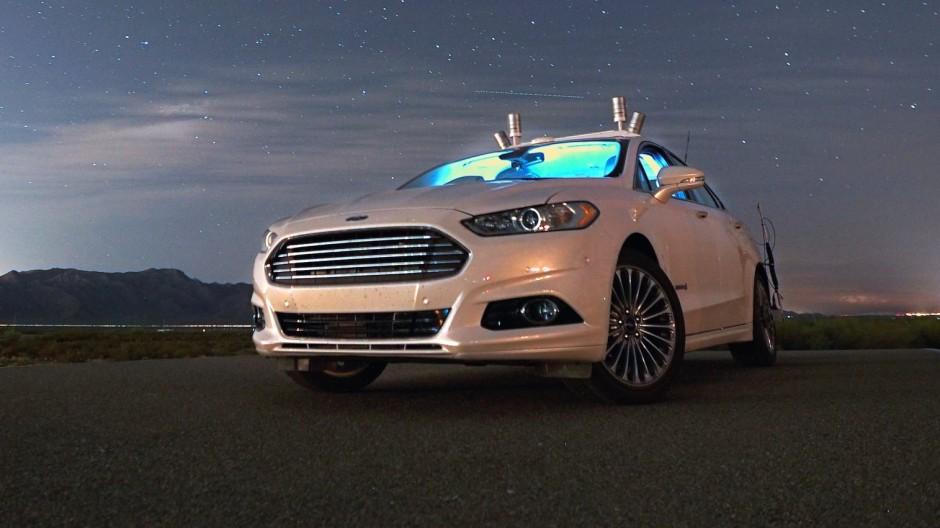 Ein autonom fahrendes Hybrid-Forschungsfahrzeug von Ford bei Nacht ohne Scheinwerfer auf einer einsamen Wüstenstraße.