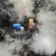 """Die Köhler prüfen mit bloßen Händen die Kohle. """"Der Rauch stört mich nicht mehr. Ich habe mich während der 35 Jahre, die ich hier arbeite, daran gewöhnt"""", meint ein Arbeiter."""