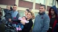 Flüchtlinge warten am Donnerstag vor einer Unterkunft in Bergisch Gladbach auf die Ankunft von Bundespräsident Gauck.