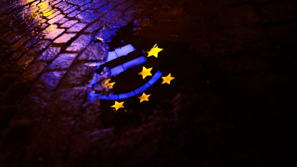 Euro sculpture is partially reflected in a puddle in front of the headquarters of the ECB headquarters in Frankfurt