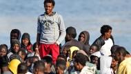 Flüchtlinge warten auf einem Boot vor der Küste Siziliens darauf an Land gehen zu dürfen.
