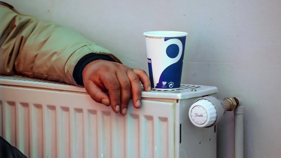 Ein Mann wärmt sich an einem Heizkörper.