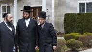 Jüdische Gemeindemitglieder stehen vor dem Haus eines Rabbis nach einem Messerangriff bei einer Chanukka-Feier am Vorabend.